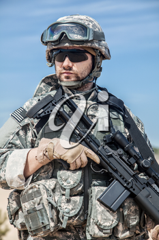 Portrait of United states airborne infantry marksman with arms, camo uniforms dress. Combat helmet on, tactical light, radio microphone, unshaven