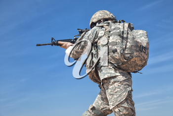 Portrait of United states airborne infantry female with arms, camo uniforms dress. Combat helmet, backpack rucksack, low angle