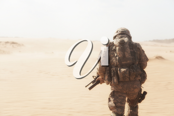 Portrait of United states airborne infantryman moving through desert storm. Cropped portrait, overcome difficulties concept
