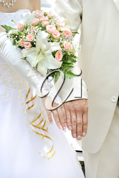 Beautiful white wedding bouquet in hands of the bride.
