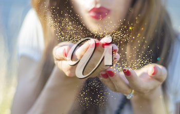Beauty young woman blowing magic gold glitter dust from her hand.