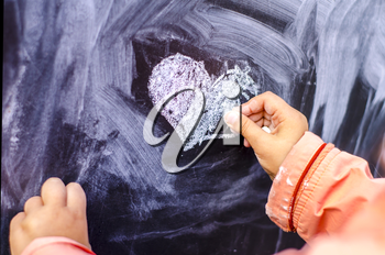 Children's drawing heart is white chalk on a black board. Valentine day is a concept photo,