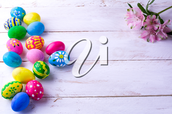 Multicolored hand-painted Easter eggs and pink flowers on white wood plank. Easter background. Easter symbol. Top view with copy space