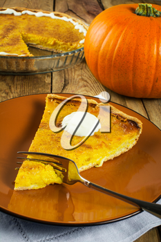 pumpkin pie slice with whipped cream on a brown plate, fork, linen napkin, glass baking dish on a wooden background