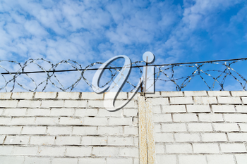 Old barbed wires and white brick wall against blue sky.