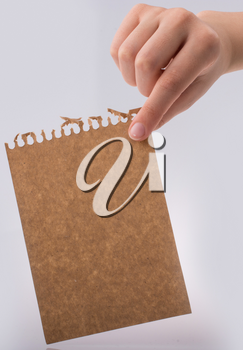 Hand holding a brown color sheet of paper on a white background