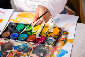 Child learning painting with colorful water colors