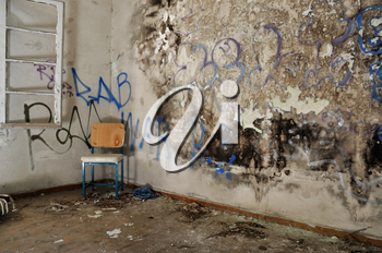Chair in decayed room interior. Peeling moldy wall and smudged paint.