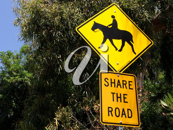 Horse crossing sign yellow with green trees near roadside