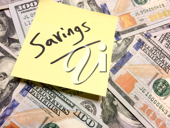 American cash money and yellow post it note with text Savings in black color aerial view