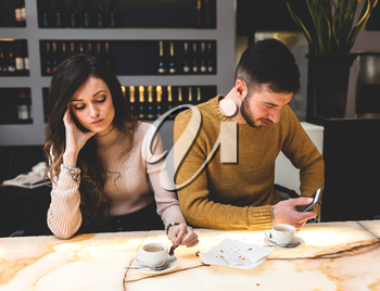Young couple at the bar. He uses the phone and she is worried and sad. Concept of betrayal.