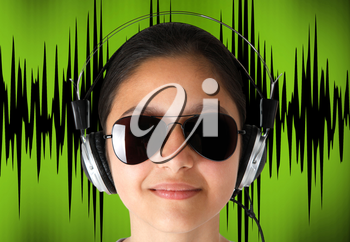 Young girl with sunglasses while listening music with headphones.