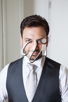 Young Italian groom with beard, brown hair and green eyes before marriage