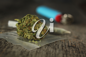 Closeup of marijuana joint and buds and blue lighter on a wooden table with a shallow depth of field