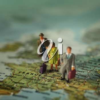 Mini people with luggage on a map, on France, Europe.