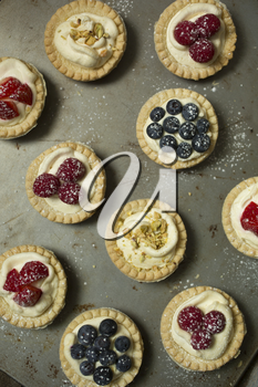Top view of blueberry, strawberry and pistachios tartlets on  biscuit sheet on a  wooden table