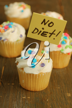 Vanilla cupcake with candies on top and no diet sign on it on a wooden background